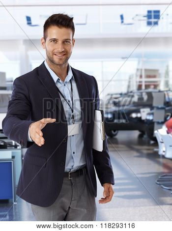 Handsome caucasian businessman shaking hands on successful deal at car saloon. Smiling, happy, looking at camera, wearing suit and name tag, clipboard under arm, hand outstretched.