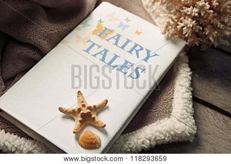 A book, seashells, stony corals and a soft blanket on the floor, close-up