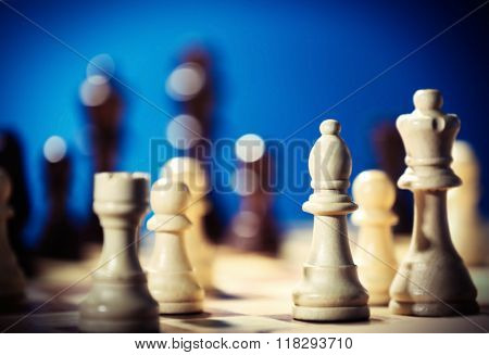 Chess pieces and game board on blue blurred background