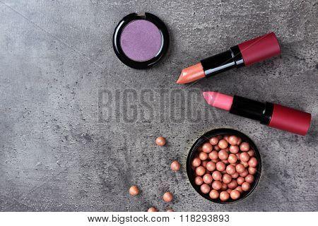Make-up lipsticks, eye-shadow and blusher, on grey background