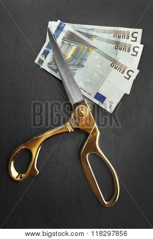 Golden scissors cut money on black background