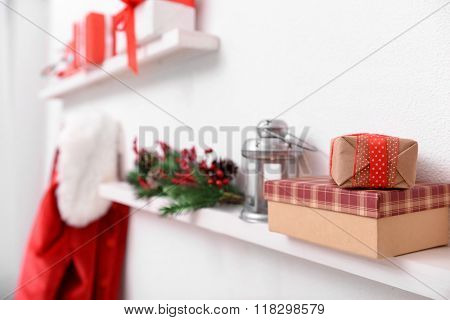 Santa costume hanging on white wall. Decorated Christmas room. Focus on shelf with gift box