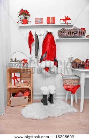 Santa costume hanging on white wall. Decorated Christmas room.