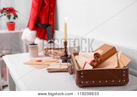 Christmas concept. Santa costume hanging in white room. Chest with wish lists on the table, close up