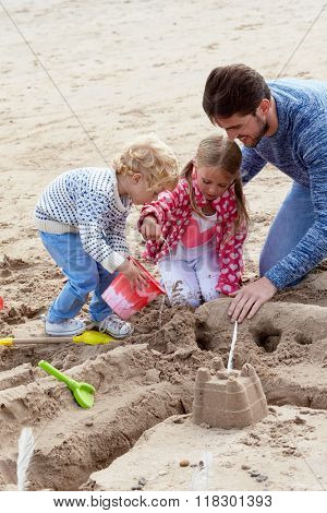 Father And Children Building Sandcastles On Beach Together