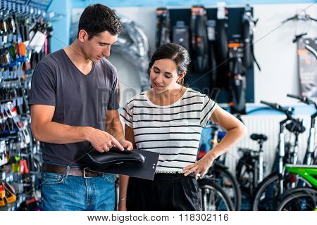 Woman buying parts in bike shop