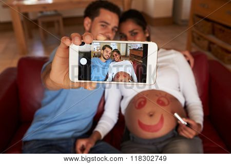 Couple Taking Selfie Of Smiley Face Drawn On Pregnant Woman's Stomach