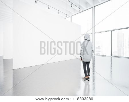 Photo of girl in  contemporary gallery looking at the blank canvas.