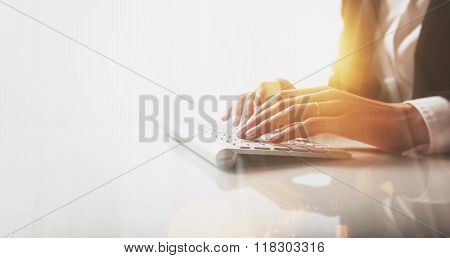 Closeup photo of female hands typing text on a wireless keyboard. Visual effects, white background
