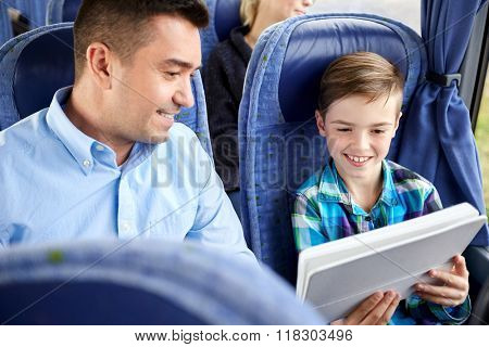 travel, tourism, family, technology and people concept - happy father and son with tablet pc computer sitting in travel bus