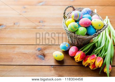 easter, holidays, tradition and object concept - close up of colored easter eggs in basket and tulip flowers on wooden table with copy space