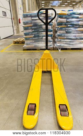 logistic, storage, loading, shipment and equipment concept - manual loader and cargo piles at warehouse
