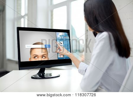 business, people, technology and internet concept - close up of woman pointing finger to web browser search bar on computer monitor in office