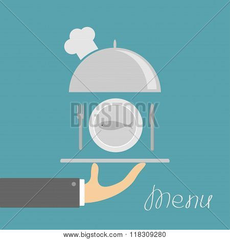 Hand Holding Silver Platter Cloche With Chefs Hat And Plate Fish, Fork, Knife. Menu Card. Blue Backg