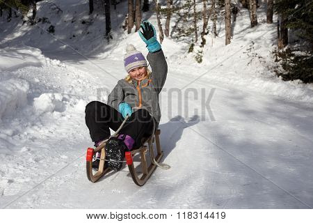 Girl On Sledge With Hand Up