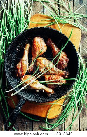 Fresh delicious fried chicken legs on a wooden chopping board decorated with fresh chives. Baked ham