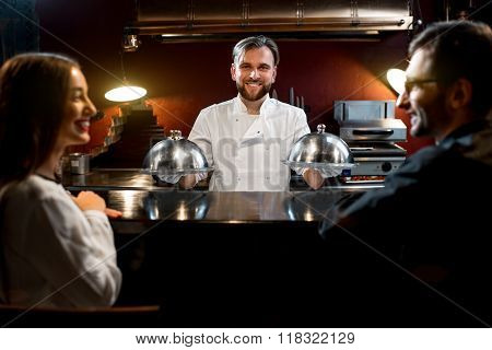 Chef cook serving dishes to the couple