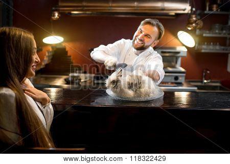 Crazy chef cook cutting alive rabbit