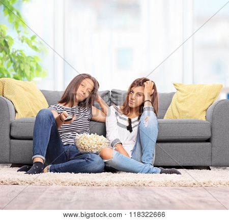 Two bored teenage girls watching TV seated on the floor in front of a gray sofa at home shot with tilt and shift lens