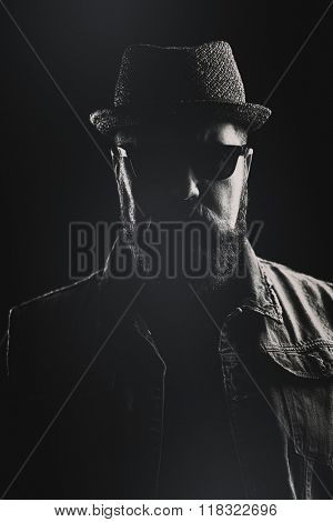 Vertical portrait of a hipster with a pork pie hat and a thick beard against a black background