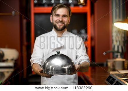 Chef cook holding cloche
