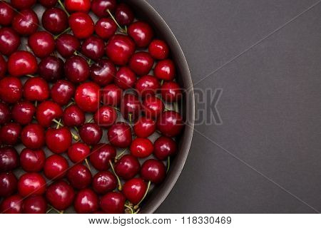 Top view of fresh red cherries in round baking tin, with copy-space for your text