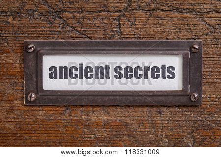 ancient secrets  tag - file cabinet label, bronze holder against grunge and scratched wood -internet publishing concept
