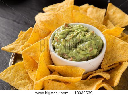 Mexican nacho chips and salsa dip on black stone background