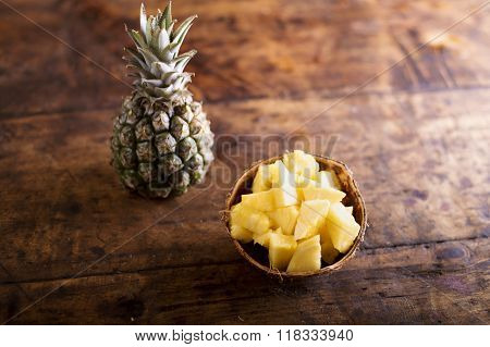 Fresh ripe pineapple, whole and chopped in a bowl