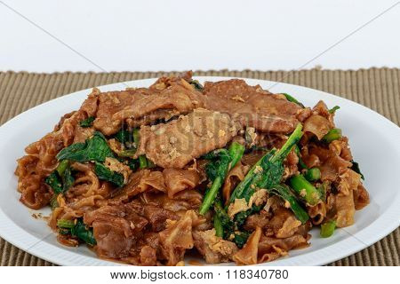 Stir fried flat noodle and pork with dark soy sauce on brown background