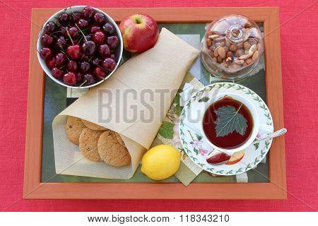 Still life with tea homemade oatmeal cookies with raisins cherries lemon apple nuts and lump sugar