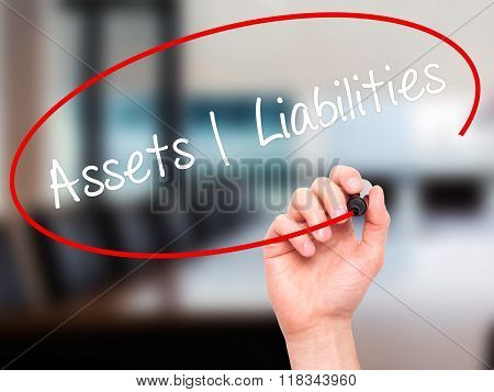 Man Hand Writing Assets Liabilities With Black Marker On Visual Screen