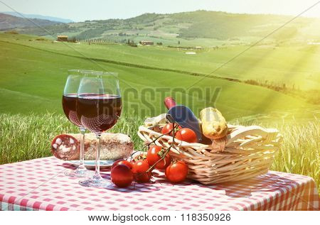 Red wine and bread on the chequered cloth against Tuscan landscape. Italy