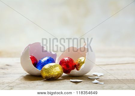 Colorful Wrapped Chocolate Eggs In A White Chicken Eggshell On A Rustic Wooden Table, Copy Space In
