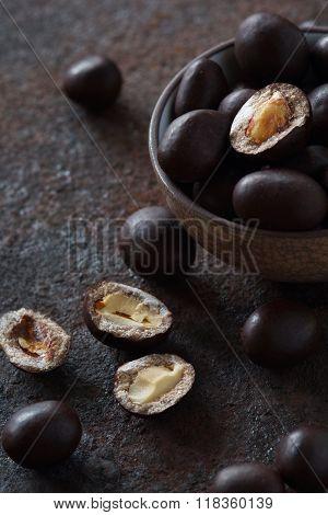 Peanuts In Chocolate On A Dark Metal
