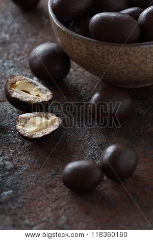 Peanuts In Chocolate On An Old Metal Surface