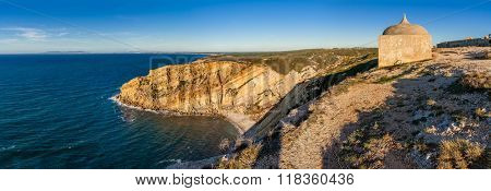 One of the promontories and bays of the Espichel Cape, with the remote Hermitage of the Sanctuary of Nossa Senhora da Pedra Mua, built on the edge of a cliff during sunset. Sesimbra, Portugal.