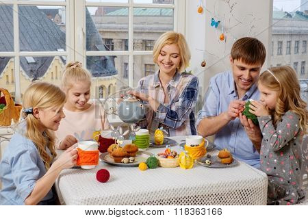 Cheerful family having fun and enjoying flavored tea with cupcakes.