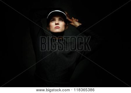 Fit Woman In Tennis Visor Looking Up Against Black Background