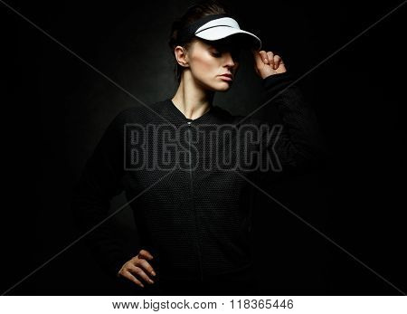 Woman Athlete Adjusting Tennis Visor Against Dark Background