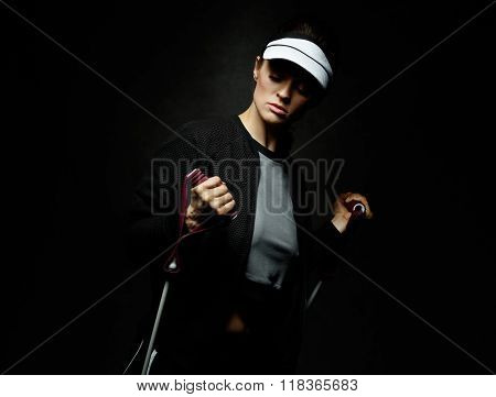 Fit Woman Training With Resistance Band Against Black Background