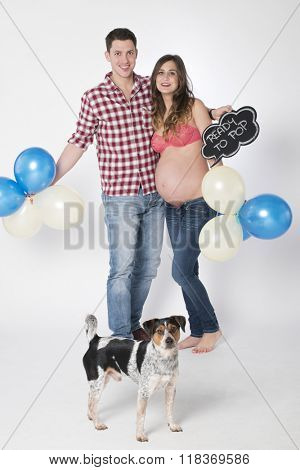 happy couple in pregnant and dog with the board ready to pop