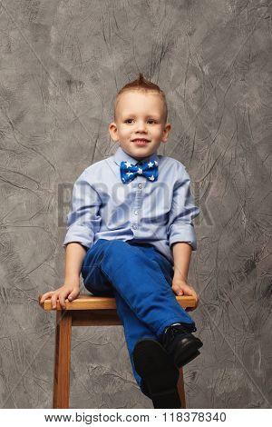 Portrait Of A Funny Little Boy Sitting On A High Stool