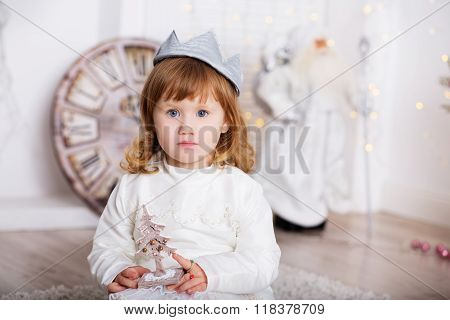 Portrait of a beautiful little girl in a white dress and a crown in the interior with Christmas decorations. Little Princess With a wooden toy Christmas tree