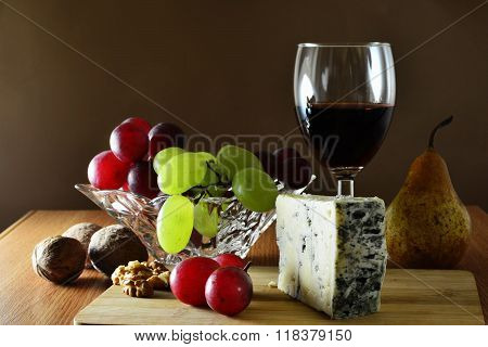 Wedge Of French Blue Veined Cheese With Grapes And Red Wine.