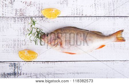 Fish on a wooden board with rosemary and lemon on a wooden vintage background