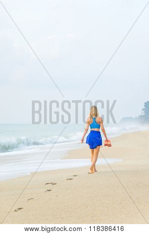 Beach travel - woman walking on sand beach leaving footprints in the sand.