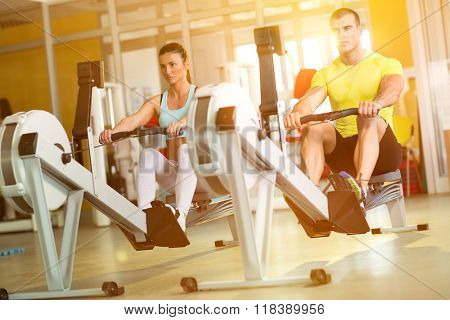 Fit  couple on row machine in gym, sport, fitness, lifestyle, and people concept