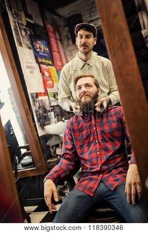 Male barber checking symmetry beard on client
