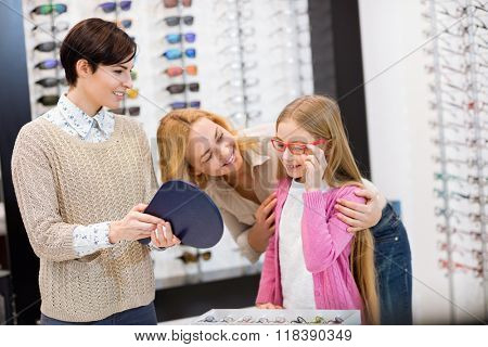 Kind saleswoman hold mirror while child try frames for eyeglasses